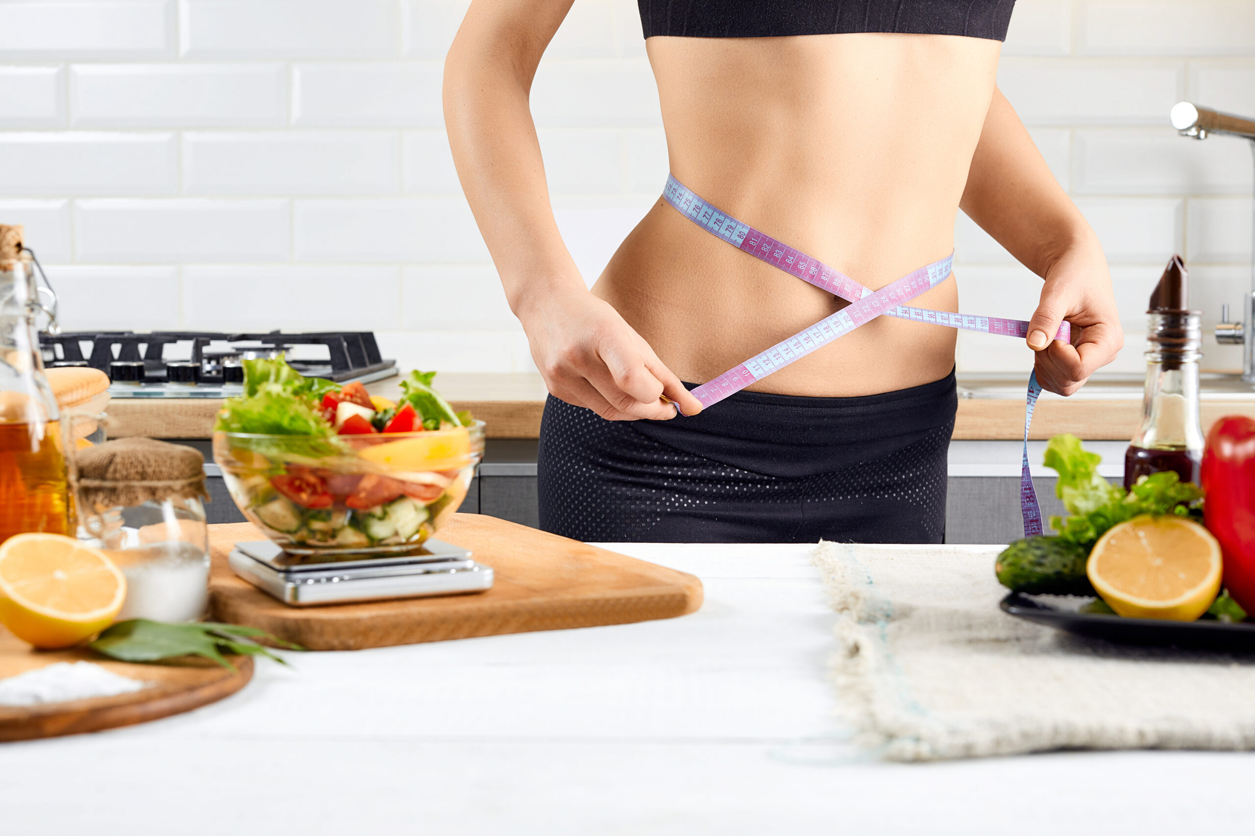 Diet, healthy eating, food and weigh loss concept. Young woman measuring waist near tomatoes, peppers and salad on the kitchen interior.